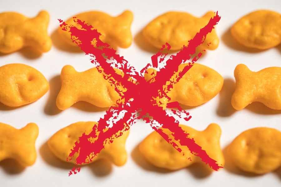 a bunch of goldfish crackers on a white background that are crossed out by a red cross